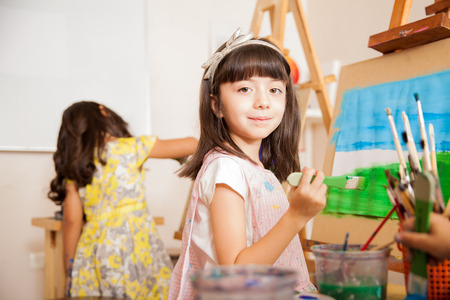 Portrait of a pretty little artist holding a brush and smiling while working on a painting for art class