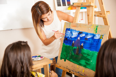 painting drawings: Pretty art teacher helping a student with her painting during art class Stock Photo