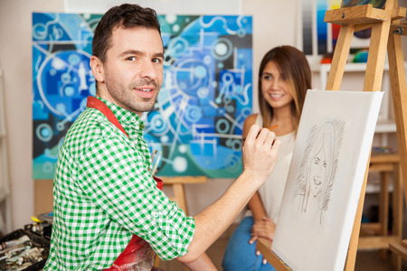 hombre pintando: Handsome male Hispanic artist drawing a sketch of a cute young woman in his studio