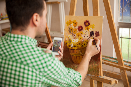 rear view: Point of view of a man copying an image from his smartphone into a painting of hir own for an art class