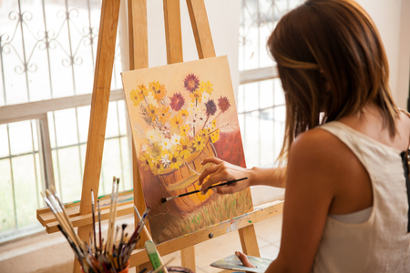 finishing touches: Rear view of a pretty female artist giving the finishing touches to her latest painting