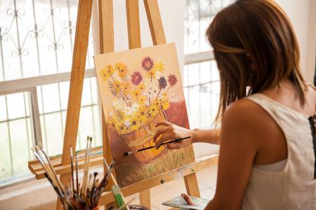 Vista trasera de un artista bastante femenina dando los toques finales a su última pintura