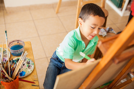 preschool children: High angle view of a cute little boy working on a painting for art class at school