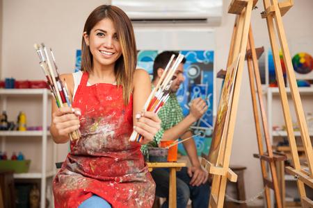 Portrét nádherná mladá brunetka na sobě zástěru a drží spoustu štětce v umělecké třídě Reklamní fotografie