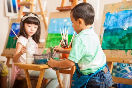 clases: Grupo de niños que trabajan en una pintura de un paisaje durante la clase de arte en la escuela