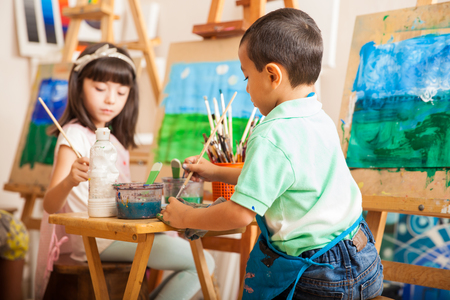 Group of kids working on a painting of a landscape during art class at school