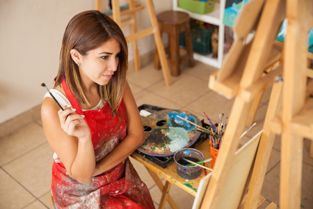 artist: High angle view of a young brunette in an apron looking at a piece of art she just finished painting