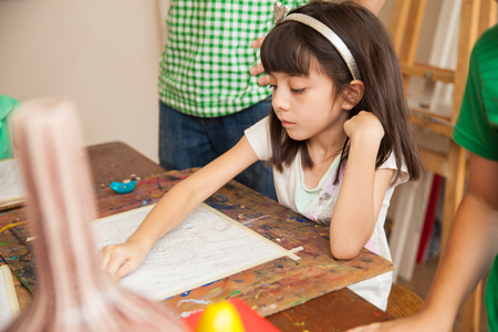 hispanic girl: Pretty little girl drawing with a pencil and copying a model during art class