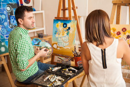 adult student: Handsome young man and women comparing their paintings while studying at an art school
