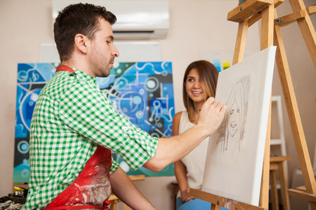 Male artist drawing a sketch of a beautiful young woman in his studio
