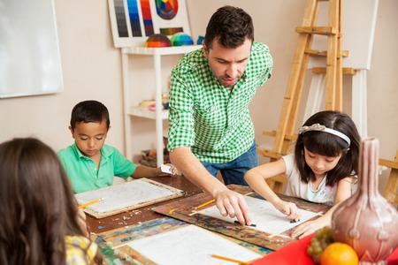 Junge attraktive männliche Kunstlehrer einer seiner Schüler mit ihrer Zeichnung während des Unterrichts helfen