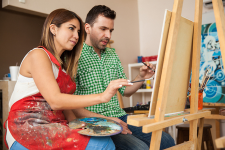 painting art: Attractive couple of young artists working together on a project at a workshop