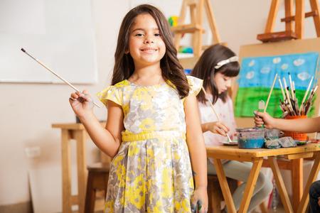 Linda niña hispana sonriendo frente a su aula durante la clase de arte