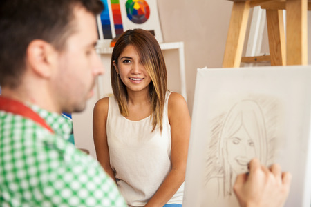 hobbies: Pretty young Hispanic woman posing as a model for a male artist and getting her portrait done Stock Photo
