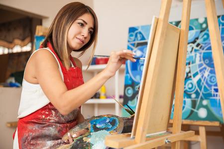 Zaměřena mladá žena umělec, který pracuje na novém obraze ve svém ateliéru Reklamní fotografie