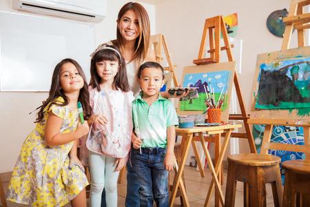 kinder: Retrato de un profesor lindo clase de arte femenino de pie con algunos de sus alumnos favoritos