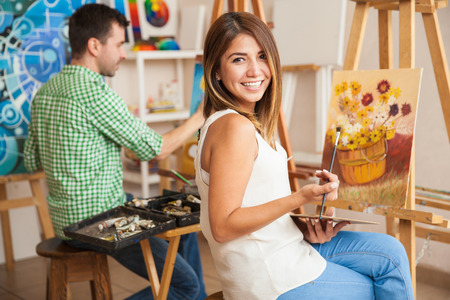 Beautiful young Hispanic woman and a handsome man attending a painting workshop together and having fun Archivio Fotografico