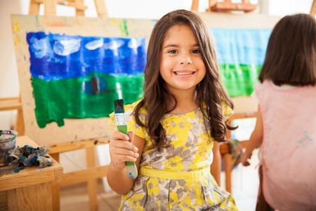 Linda chica latina celebración de un pincel y sonriente durante la clase de arte en la escuela