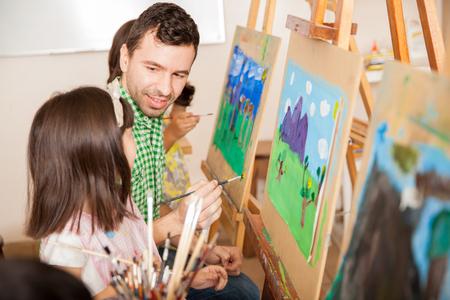 maestra preescolar: Apuesto profesor joven que trabaja en una pintura con una de sus estudiantes durante la clase de arte Foto de archivo