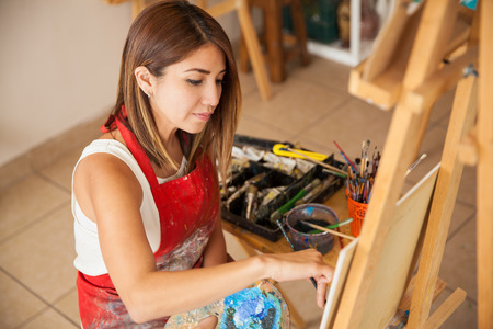 High angle view of a young artist wearing an apron and working on a painting in her studio Imagens