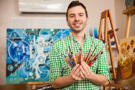 artist: Portrait of a handsome young artist holding a bunch of paintbrushes in his workshop and smiling Stock Photo