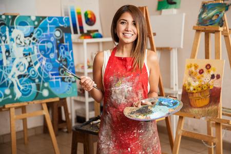 Portret pięknej artystki pracuje nad kilkoma projektami artystycznymi w swoim studio