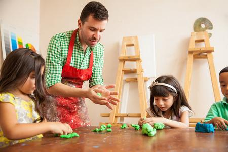 Professor de arte masculino atrativo e seus alunos trabalham com um pouco de argila para esculpir classe Imagens