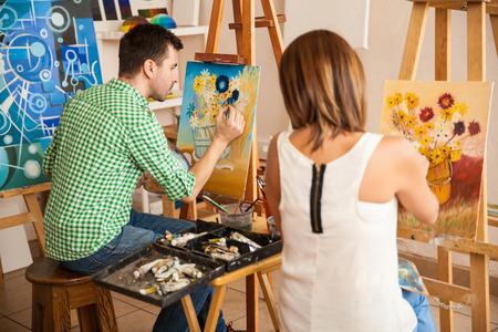 Achteraanzicht van een paar jonge volwassenen werken aan hun eigen schilderijen tijdens zijn studie aan de kunstacademie