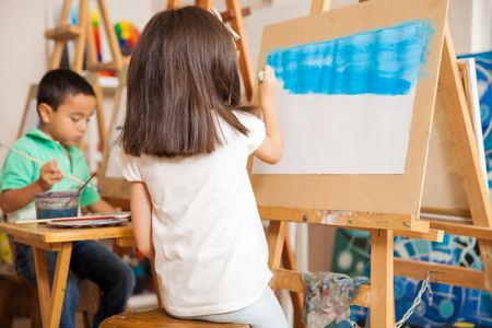 preschool classroom: Rear view of a little girl painting the sky of a landscape for her art class