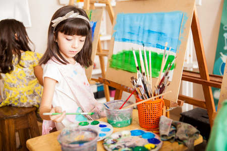 children art: Cute girl mixing some colors for her painting in art class at school Stock Photo