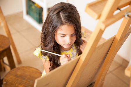 preschool children: High angle view of a cute little brunette painting during art class