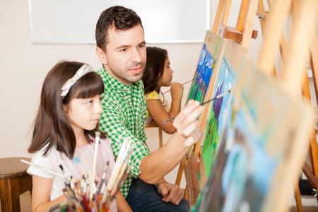 Portrait of an attractive Hispanic art teacher helping a little girl with her painting