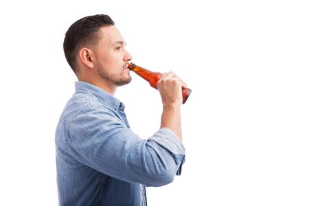 hombre tomando cerveza: Vista de perfil de un joven hombre de la cerveza que bebe de una botella contra un fondo blanco Foto de archivo