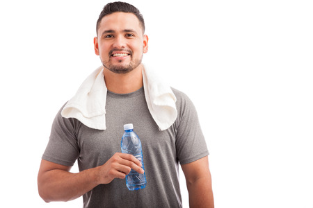 towel: Portrait of a young Hispanic male athlete with a towel around his neck and a bottle of water relaxing and cooling down on a white background