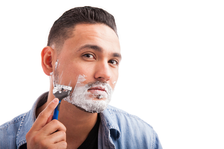full length mirror: Young Hispanic man looking at the camera as if it was a mirror and using a razor to shave his beard on a white background Stock Photo