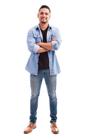 Stattliche lateinische junge Mann lässig gekleidet und mit den Armen steht vor einem weißen Hintergrund gekreuzt