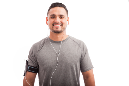 earbuds: Portrait of a young happy athlete wearing an armband and earbuds on a white background