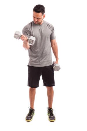 pesas: Retrato de cuerpo entero de un joven en traje deportivo levantar pesas y trabajar en su bíceps