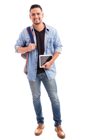 Handsome college student carrying a school bag and a tablet computer on a white background 写真素材