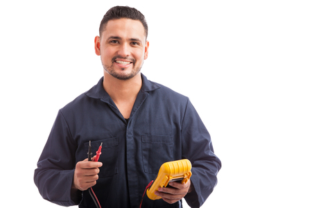 Portrait of a young Hispanic electrician wearing overalls using a multimeter and smiling on a white background Stockfoto