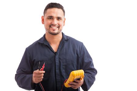 Retrato de un electricista hispana joven que llevaba un mono con un multímetro y sonriente sobre un fondo blanco Foto de archivo