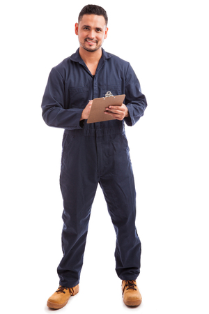 single: Hispanic young electrician wearing overalls and reviewing a checklist on a white background