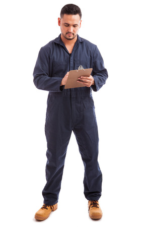 worker man: Full length portrait of a young electrician going through an inspection checklist on a white background Stock Photo