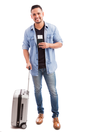 good looking guy: Full length portrait of a good looking guy carrying a suitcase and his passport before going on vacation