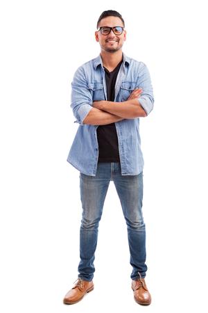 Volledige lengte van een jonge man draagt een bril en terloops gekleed tegen een witte achtergrond