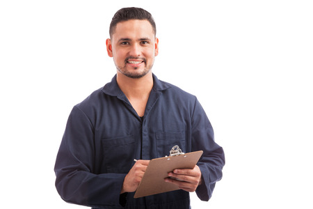 home inspection: Portrait of a young handsome contractor going through a home inspection on a white background