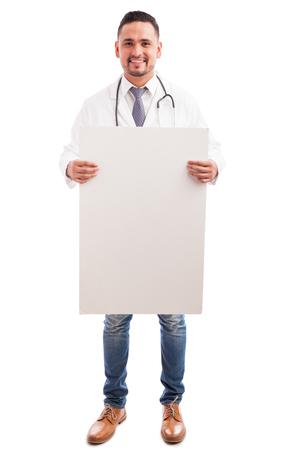 bata blanca: Retrato de cuerpo entero de un joven médico hispana con una bata de laboratorio y un estetoscopio con un cartel en blanco