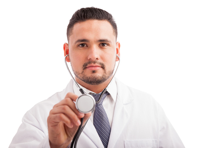 Attractive young doctor with a beard using a stethoscope to examine a patient against a white background Imagens