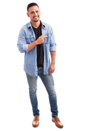 man shirt: Full length portrait of a young Latin guy smiling and pointing to his side towards copy space