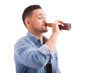 Portrait of a drunk man drinking beer from a bottle in a white background